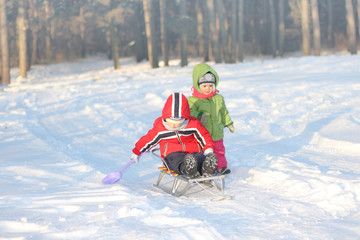 Children play on a sled in the snow