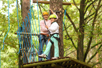 mother and daughter overcome obstacles between high trees
