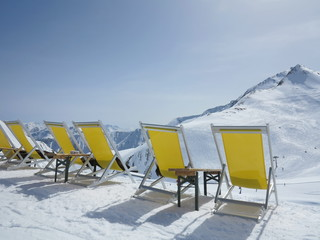 Row of deck chairs overlooking an Alpine peak