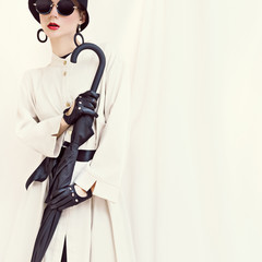 Retro styled fashion girl with umbrella. glamorous portrait