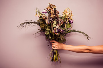 Hand with dead flowers
