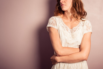 Young woman in white dress standing by purple wall