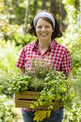 Junge Frau mit Kräutern im Garten, young woman with herbs in a