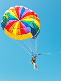 girl parascending on parachute in blue sky
