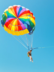 girl parascending on parachute in blue sky