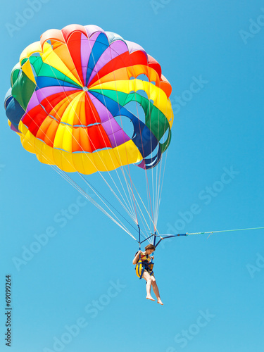 Aluminium Luchtsport girl parascending on parachute in blue sky