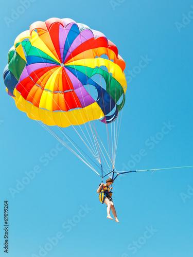 Plexiglas Luchtsport girl parascending on parachute in blue sky