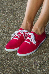 Female feet in red gym shoes