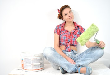 Beautiful young woman with roller thinks over idea of repair