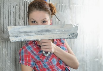 Young beautiful girl with pallets stay near the repaired wall