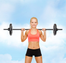 smiling sporty woman exercising with barbell
