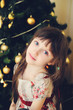 Girl being happy about christmas tree and lights.