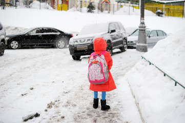 kid girl walks from school  on winter day