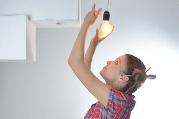 Young beautiful woman twists a bulb
