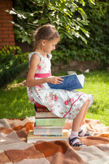 girl in cute dress sitting on pile of books and reading