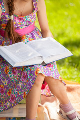 cute girl reading big book at meadow
