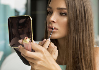 Woman putting lipstick and looking in mirror