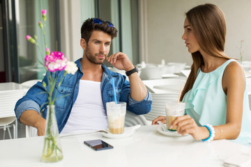 Attractive couple in restaurant drinking frappe