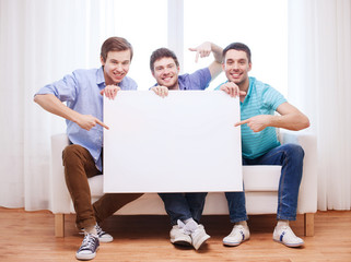 happy male friends with blank white board at home