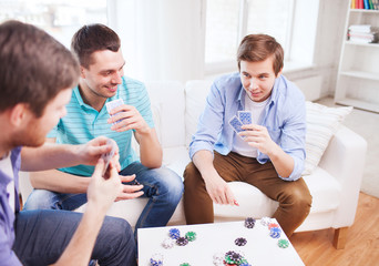 three smiling male friends playing cards at home