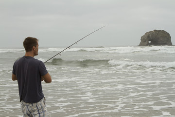 Man fishing in the surf on Rockaway beach