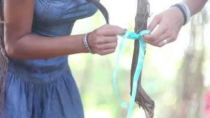 girl decorator tying ribbons on the branches on the wedding