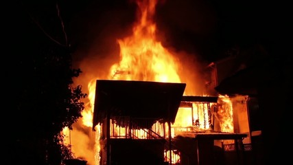 House fire fully involved in flames and spreading to houses