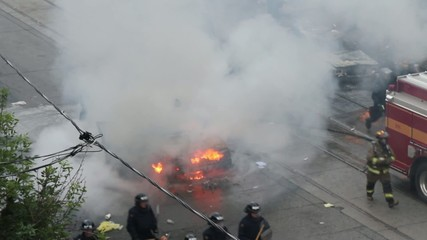 Riot officers and fireman walking around car fire with smoke