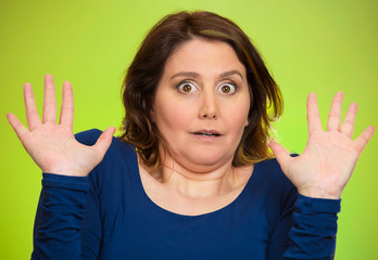 Shocked scared middle aged woman green background