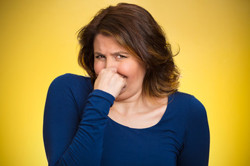 Woman pinches her nose, bad smell, yellow background