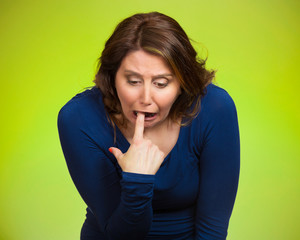 Sick woman sticking finger in throat vomiting, green background