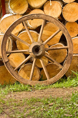 Old wagon wheel on a background of wood