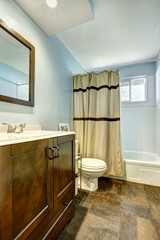 Bathroom with brown tile floor and light blue walls