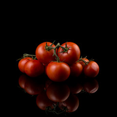 Red tomatoes with stems on dark background