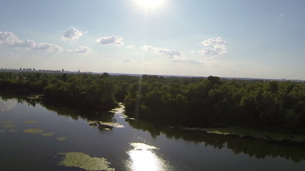 Evening  flight over  river with sun on sky . Aerial view