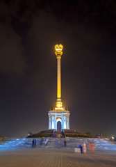 Night view of stele with the emblem Tajikistan. Dushanbe