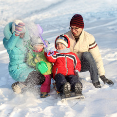 family of four has fun in the snow in winter