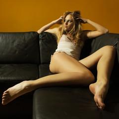 Pretty woman in lingerie posing near the sofa