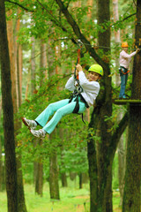 Climber girl child engaged in training between trees