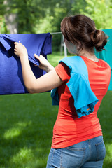 Woman removing laundry from clothesline