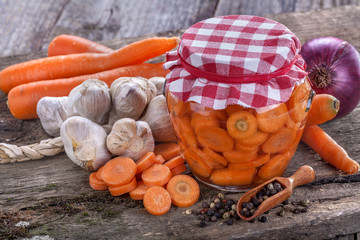 Domestic carrot canned in a jar and on the old rustic table