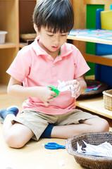 Little boy cutting paper of montessori educational