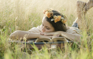 A young girl sleeping with her head on a book