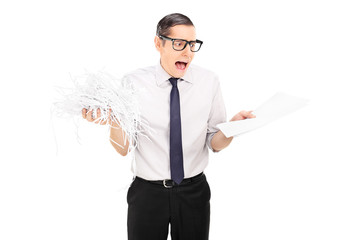 Shocked businessman holding shredded documents