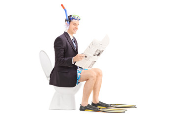 Man with snorkel reading the news on a toilet