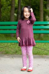 Smiling asian girl in park