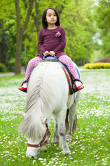 Asian girl sitting on pony