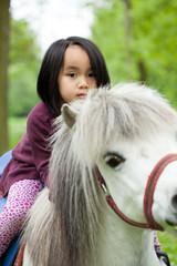 Asian girl on little horse