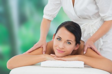 Beautiful brunette enjoying a back massage smiling at camera