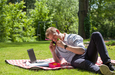 Businessman eating sandwich and talking on the phone